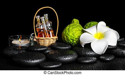 Aromatic spa setting of bergamot fruits, candles, plumeria flower and bottles essential oil on zen stones, closeup
