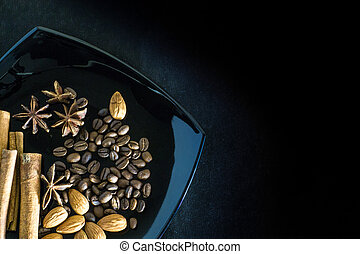 Aromatic spices with coffee beans and almonds on a black background