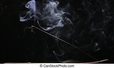 Aromatic stick smoldering on black background - Aromatic...