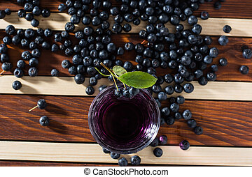 Aronia spilled on wooden table with glass of aronia juice