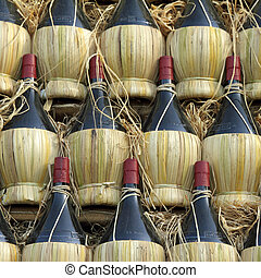 arranged many chianti wine bottles ( traditionally in straw ...