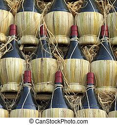 arranged many chianti wine bottles ( traditionally in straw basket, called fiasco, plural fiaschi ),Florence, Tuscany, Europe