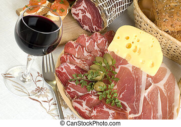 arranged prosciutto, wine, olives cheese, bread and tomato close up