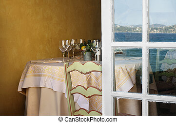 Arranged table in a restaurant and open window. Reflection...