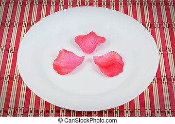 Arrangement of rose petals on a plate. On a red napkin.