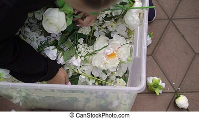 Arranging artificial flowers decoration. Young woman florist work making organizing diy artificial flower, craft and hand made concept.