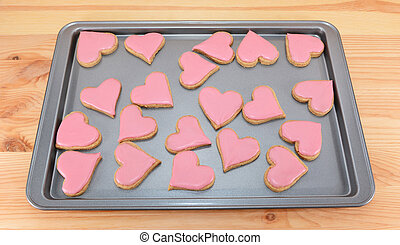 Array of heart-shaped cookies with pink frosting