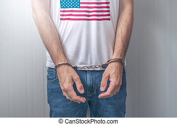 Arrested man with cuffed hands wearing shirt with USA flag