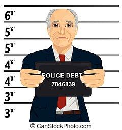 Arrested senior businessman posing for mugshot holding a...