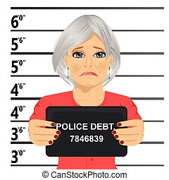 Arrested senior woman posing for mugshot holding a signboard...