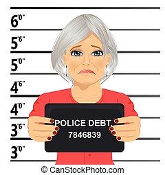 Arrested senior woman posing for mugshot holding a signboard...