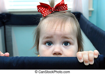 Arresting Eyes - Baby girl stands at her play pen rim and...