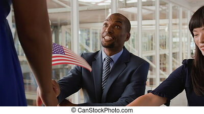 Close up front view of a smartly dressed young African American man sitting at a desk at the entrance to a political rally smiling and giving a US flag to an arriving attendee