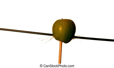 Arrow shooting through green apple