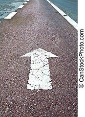 Arrow sign on asphalt surface