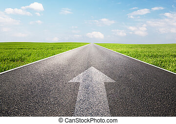 Arrow sign pointing forward on long empty straight road, ...