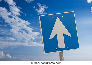 Arrow sign against bright blue sky with white clouds