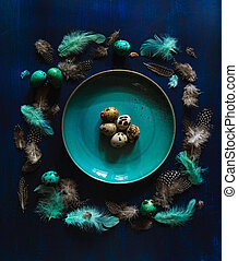 Arrrangement of quail eggs and feathers, some colored teal, plate on dark blue background. Dark moody Easter card
