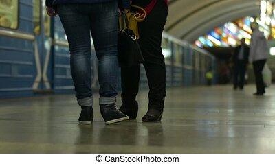 Arrrival of subway train. People in metropolitan platform waiting for train.