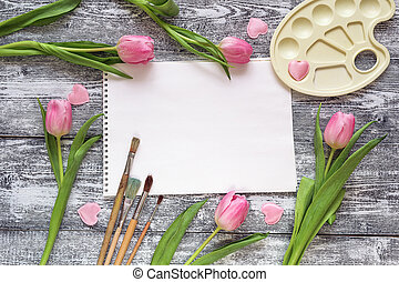 Art album, paintbrushes, palette and pink tulips on gray wooden background. Copy space
