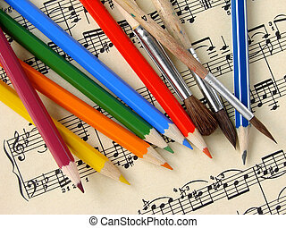 color pencils and paintbrushes on the musical notes background