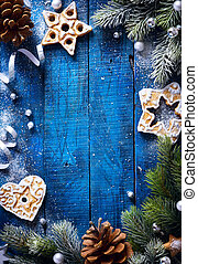 art Christmas blue wooden background with snow fir tree and Christmas cookies
