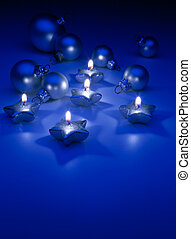 Art Christmas candles and ornaments on a blue background -...