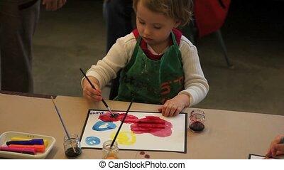 Cute little baby girl having fun painting at art class