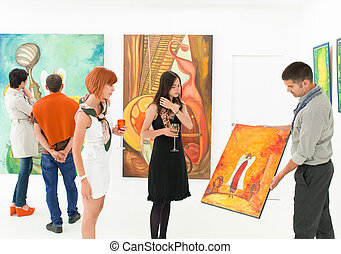 man holding and showing a colorful painting to other people in an art gallery