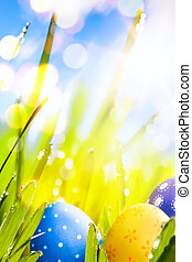 art Colorful Easter eggs decorated  in the grass on blue sky bac