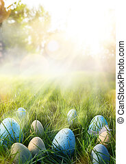 art Colorful Easter eggs in the grass on sky background