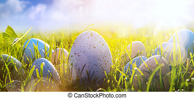 art Colorful Easter eggs on the grass on blue sky background