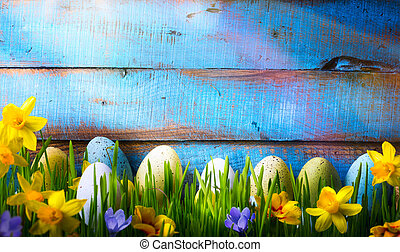 art Easter Background with easter eggs and spring flowers on green grass