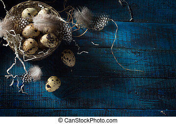 art Easter banner with eggs and feathers in silver basket on dark blue background. Top view, flat lay with copy space.