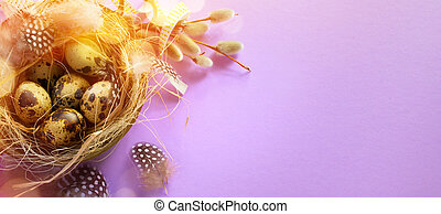 Art Easter banner with eggs, bird feather and spring flowers on pink background. Top view, flat lay with copy space.