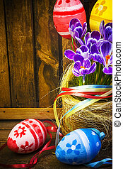 Art Easter decoration with handpainted eggs in basket and crocus on wooden background