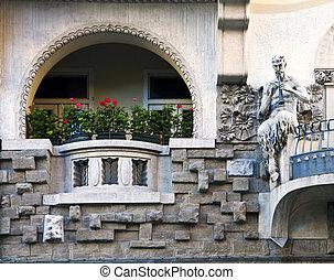 Art nouveau building facade with faun playing flute