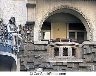 Art nouveau facade with statue of young woman sitting on a balk