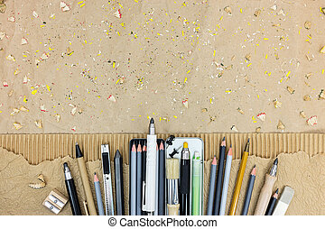 different drawing tools on brown paper background with pencils shavings