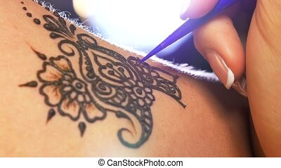 Art of mehendi. Master starts working on models back, close...