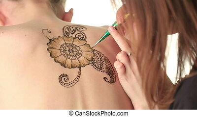 Art of mehndi. Master draws on girl's back, close-up