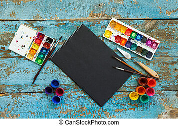 Painting set: brushes, paints, crayons, watercolor, black paper on a blue wooden background