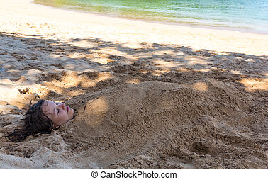 Art photo of beautiful lady buried in the sand
