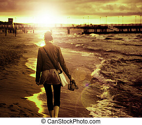 Art picture of young woman walking by the seaside