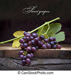 art purple grapes on old wooden background - A bunch of...