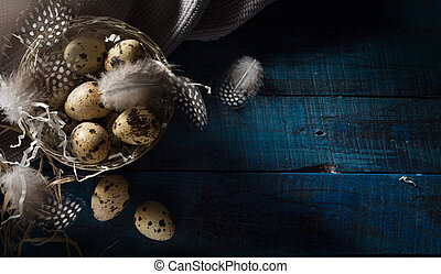 Art Retro style picture with Easter eggs and feathers in silver basket on dark blue background. Easter banner background; Top view, flat lay with copy space.