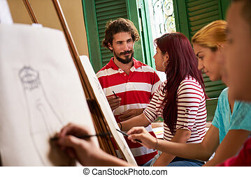Art School With Teacher And Students Painting In Class