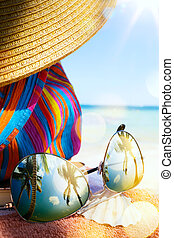 art Straw hat, bag and sun glasses on a tropical beach