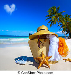 Art Straw hat, bag, sun glasses and flip flops on a tropical beach