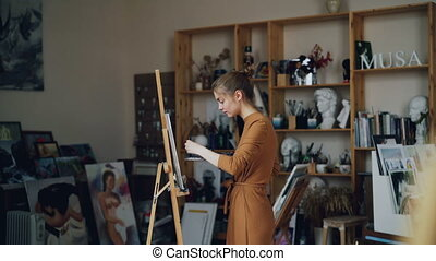 Art student is working in studio alone painting picture with...